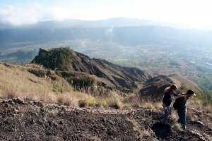 Гид помогает спуститься с вулкана Батур. Бали